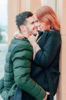 Glückliches liebendes paar, das auf der straße lächelt und umarmt. zwei glückliche menschen liebesgeschichte - medium shot portrait