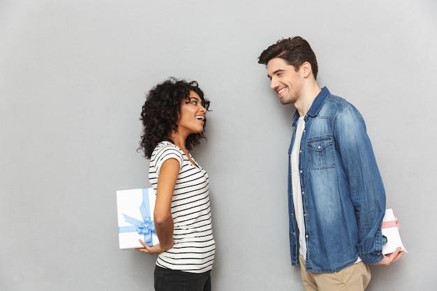 Glückliches liebendes paar, das geschenkboxen für einander hält.