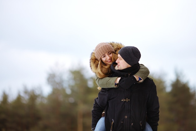 Glückliches liebendes paar, das im verschneiten winterwald zusammen im freien geht