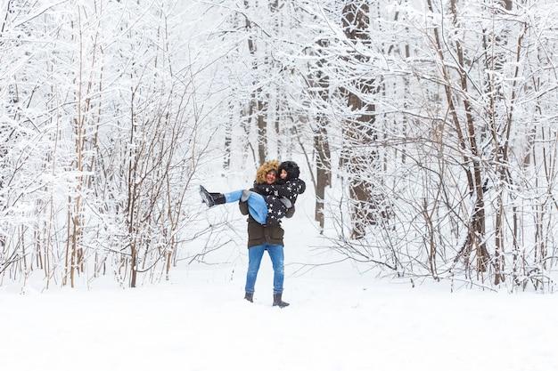 Glückliches liebendes paar, das spaß draußen im snowpark hat.