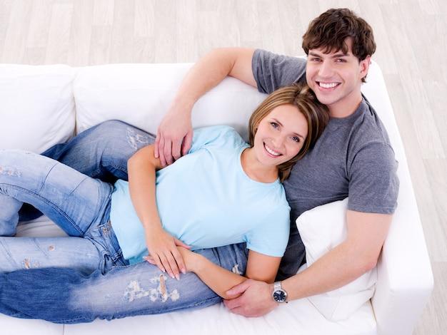 Glückliches liebendes paar, das zusammen auf dem sofa im lässigen - hohen winkel liegt