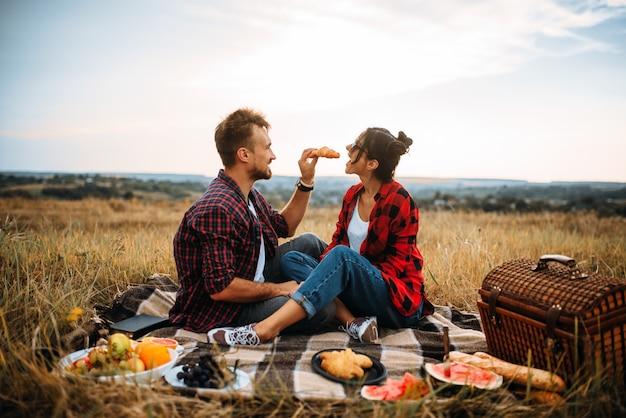 Glückliches liebespaar auf picknick im sommerfeld. romantisches junket von mann und frau