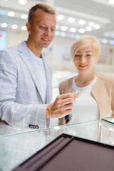 Glückliches liebespaar, das eheringe im juweliergeschäft wählt. mann und frau wählen golddekoration. zukünftige braut und bräutigam im juweliergeschäft