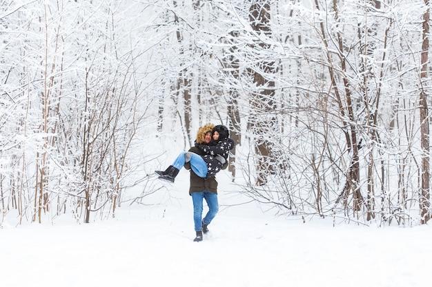 Glückliches liebespaar, das spaß im freien im schneepark-winterurlaub hat