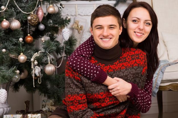 Glückliches liebespaar, das weihnachten feiert, das vor dem weihnachtsbaum sitzt, sich umarmt und in die kamera lächelt