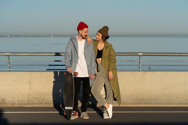 Glückliches liebespaar hipster mit longboard auf der brücke bei sonnenschein lächelnd in stilvoller kleidung