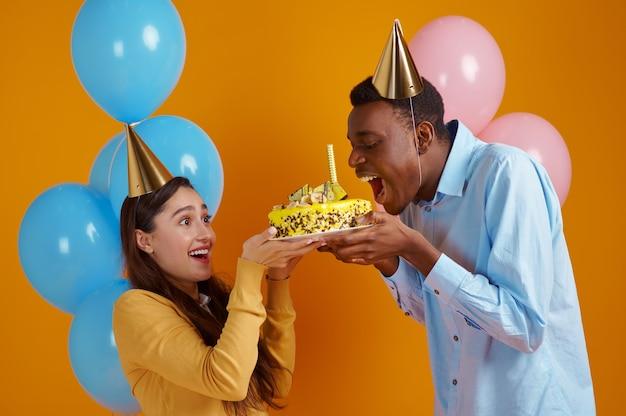 Glückliches liebespaar in mützen, die geburtstagskuchen mit feuerwerk halten. hübsches familienfest, event oder geburtstagsfeier, ballondekoration