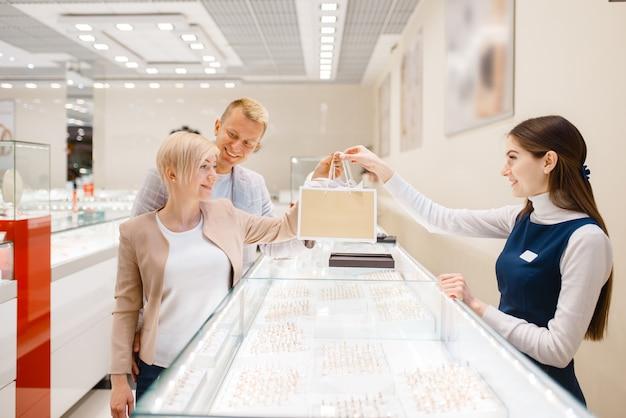Glückliches liebespaar kauft im juweliergeschäft ein.