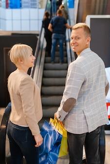 Glückliches liebespaar mit einkaufstüten an der rolltreppe