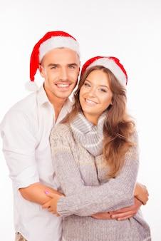 Glückliches liebespaar mit weihnachtsmützen