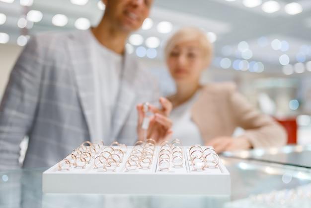 Glückliches liebespaar nahe der schachtel mit vielen eheringen im juweliergeschäft. mann und frau wählen golddekoration. zukünftige braut und bräutigam im juweliergeschäft
