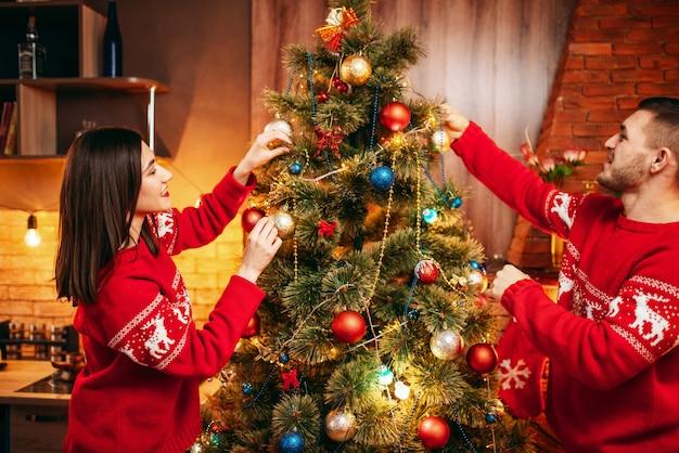 Glückliches liebespaar schmücken weihnachtsbaum. weihnachtsfeier, fröhlicher mann und frau, die spaß zusammen haben