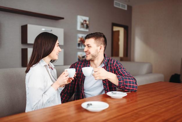 Glückliches liebespaar trinkt kaffee am holztisch