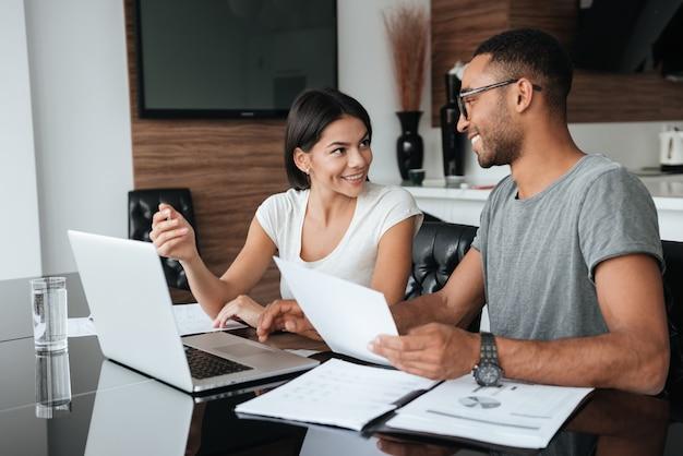 Glückliches liebevolles junges paar, das laptop verwendet und ihre finanzen mit dokumenten analysiert. einander ansehen.