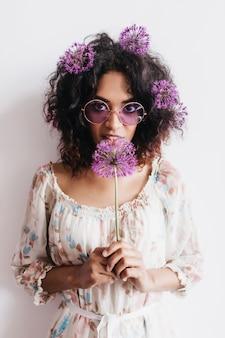 Glückliches lockiges afrikanisches mädchen, das lila allium hält. stilvolle brünette frau, die mit blumen aufwirft.