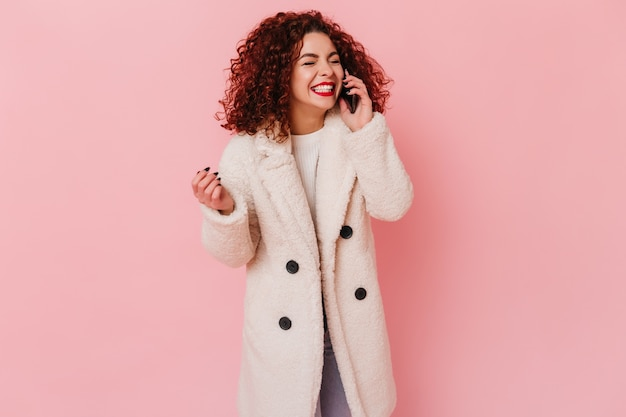 Glückliches lockiges brünettes mädchen im weißen öko-mantel, das glücklich am telefon auf rosa raum spricht.