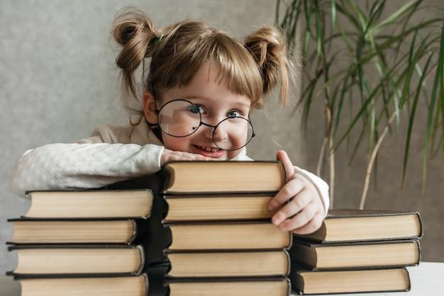 Glückliches lustiges baby in den gläsern, die ein buch lesen. emotionales mädchen. bald zur schule. speicherplatz kopieren.