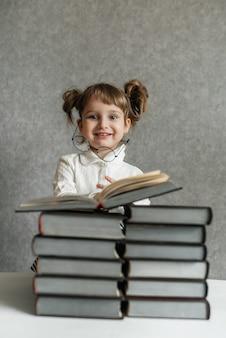 Glückliches lustiges baby in den gläsern, die ein buch lesen. emotionales mädchen. bald zur schule.
