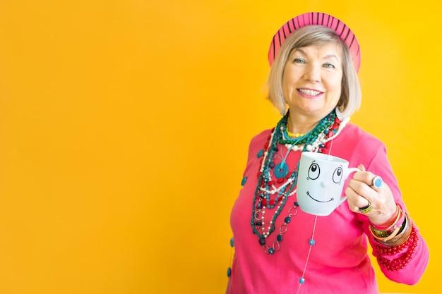 Glückliches lustiges gesicht der älteren frau, das eine tasse kaffee oder tee in der stilvollen kleidung trinkt