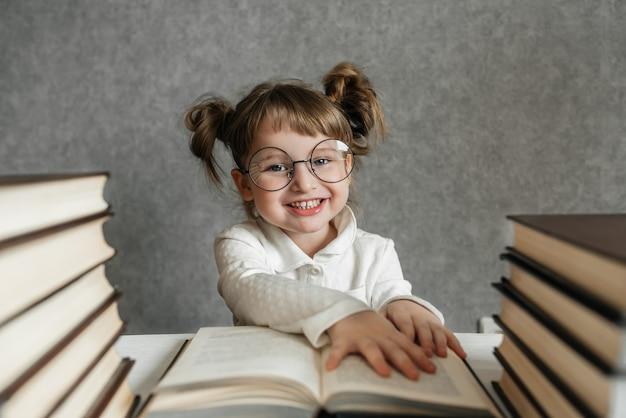 Glückliches lustiges kaukasisches baby in den gläsern, die ein buch lesen. emotionales mädchen. bald zur schule.