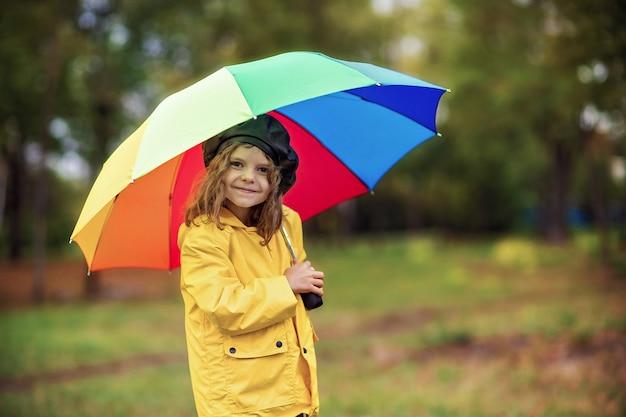 Glückliches lustiges kindermädchen mit mehrfarbenregenschirm in den gummistiefeln am herbstpark
