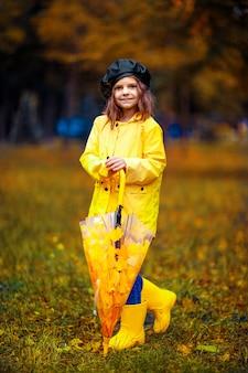 Glückliches lustiges kindermädchen mit mehrfarbigem regenschirm in gummistiefeln am herbstpark.