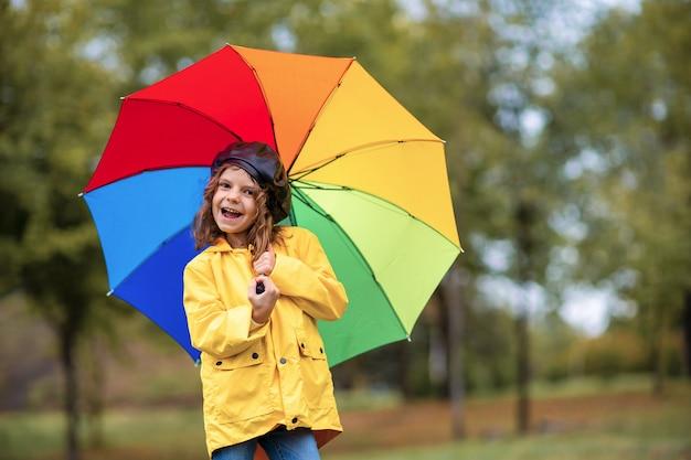 Glückliches lustiges kindermädchen mit regenschirm in den gummistiefeln