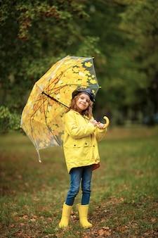 Glückliches lustiges kindermädchen mit regenschirm in gummistiefeln
