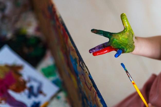 Glückliches lustiges kindermädchen zeigt die hände, die mit farbe schmutzig sind
