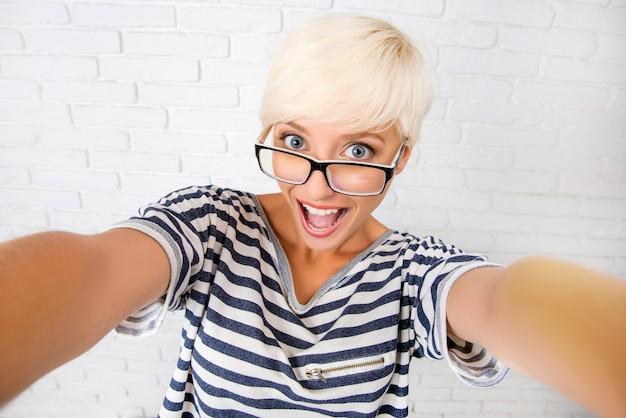 Glückliches lustiges mädchen mit brille und kurzen haaren