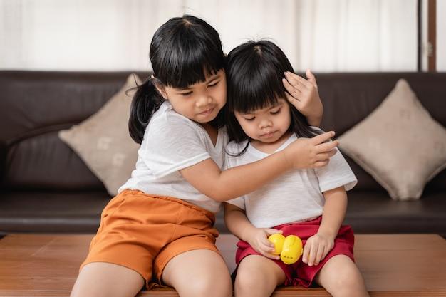 Glückliches lustiges mädchen zwei schwestern, die mit liebe umarmen und lachen