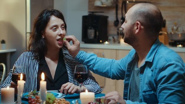 Glückliches lustiges paar in der liebe, das trauben beim abendessen isst, lächelt und spaß beim romantischen abendessen hat. ehefrau und ehemann feiern jubiläum mit rotwein, zarte momente bei kerzenlicht in der küche