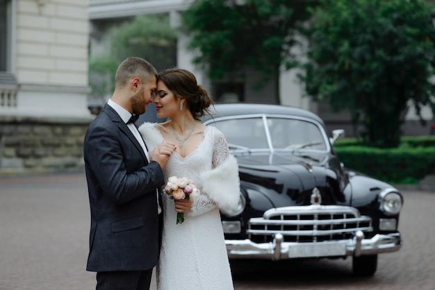 Glückliches luxushochzeitspaar, das nahe retro mit blumenstraußauto im herbst küsst und umarmt