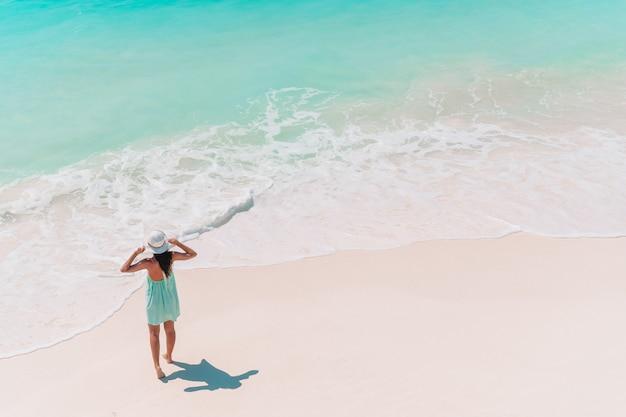 Glückliches mädchen am strand, der viel spaß im seichten wasser hat