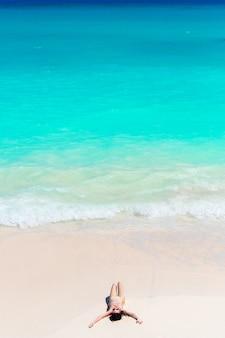 Glückliches mädchen am strand im seichten wasser mit kleinen wellen. draufsicht des schönen mädchens auf der küste
