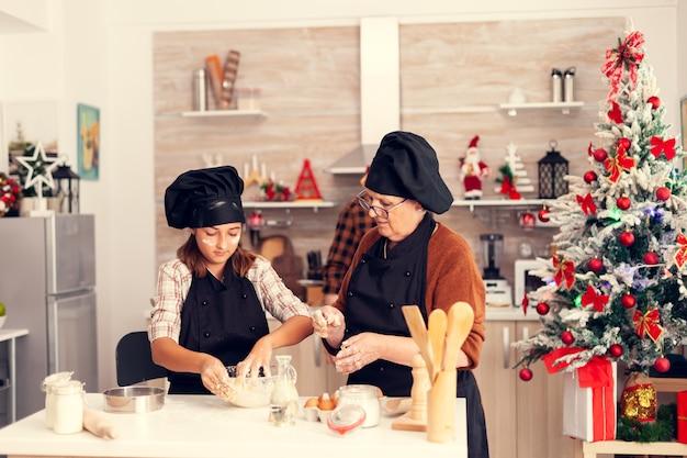 Glückliches mädchen am weihnachtstag mit schürze, die kekse macht
