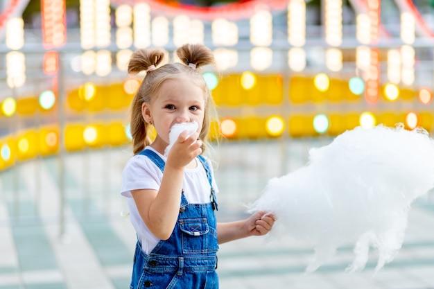 Glückliches mädchen an einem vergnügungspark, der im sommer zuckerwatte isst