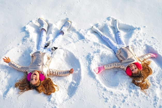 Glückliches mädchen auf einem schneeengel zeigt.