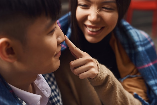 Glückliches mädchen berührt guy nose asian couple flirting.