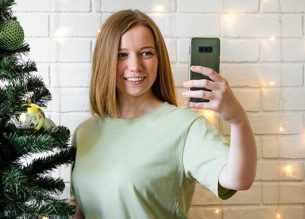 Glückliches mädchen chattet mit freunden am telefon. konzept online weihnachten