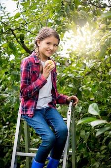 Glückliches mädchen, das am hellen sonnigen tag reife äpfel im garten pflücken