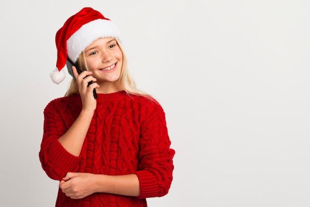 Glückliches mädchen, das am mittleren schuss des telefons spricht