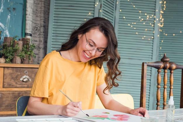 Glückliches mädchen, das aquarell in ihrem arbeitsplatz skizziert