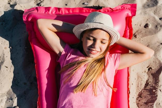 Glückliches mädchen, das auf aufblasbarer matratze auf sand sich entspannt