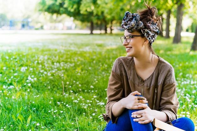 Glückliches mädchen, das auf einem grünen rasen im park an einem sonnigen sommertag sitzt