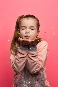 Glückliches mädchen, das auf einem rosa hintergrund feiert. sprengt bunte konfetti