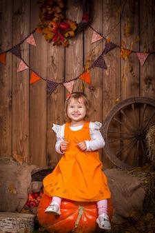 Glückliches mädchen, das auf einem sehr großen orange kürbis unter dem heu sitzt
