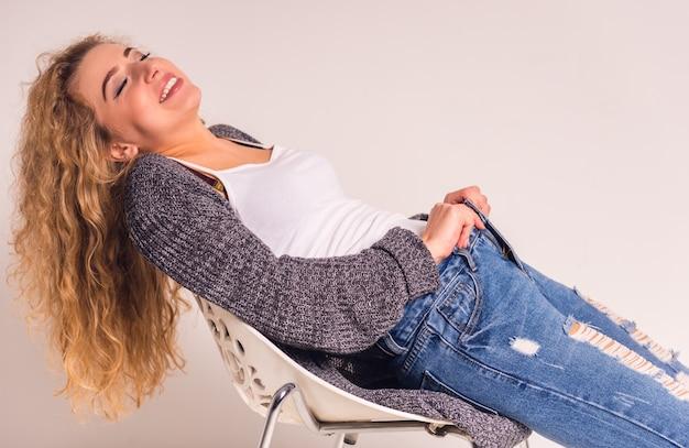 Glückliches mädchen, das auf einem stuhl in der blue jeans im studio sitzt.