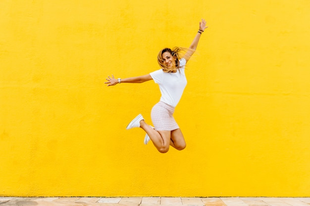 Glückliches mädchen, das auf einen gelben hintergrund springt
