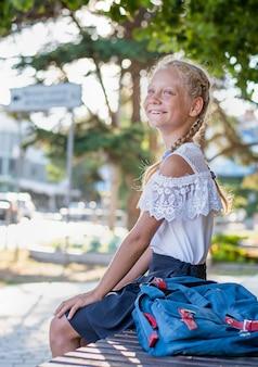 Glückliches mädchen, das auf einer bank mit einem rucksack sitzt
